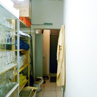 На фото: часть помещения коридора, стены окрашены, полы - плитка, слева вдоль стены - стеллажи для посуды и хозяйственной утвари, на заднем плане - тамбур и дверь запасного выхода