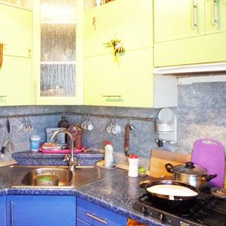 На фото: часть помещения кухни, кухонный гарнитур - столы-тумбы с общей столешницей и навесные шкафы, металлическая угловая мойка со смесителем, справа от нее - газовая варочная панель на 4 комфорки, над варочной панелью - вытяжка, кухонный фартук облицован керамической плиткой