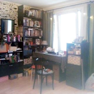 На фото: часть помещения жилой комнаты, одно большое широкое окно, у окна - тумба и письменный стол со стулом и табуретом, слева от окна у стены - стеллаж от пола до потолка с книгами, левее - комод с двумя открытыми и одной закрытой полкой, над комодом на стене - зеркало, полы - ламинат, стены оклеены обоями, на стене справа и слева от окна - точечные светильники