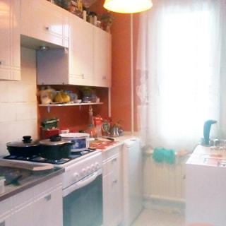 На фото: часть помещения кухни, одно окно, под окном - радиатор батареи центрального отопления, слева от окна вдоль стены - стиральная машина, тумба-стол, четырехкомфорочная газовая плита с духовым шкафом, тумба-стол с металлической мойкой, над столами на стене - навесные кухонные шкафы, фартук у плиты облицован керамической плиткой, справа от окна у стены - тумба-стол, на потолке - люстра