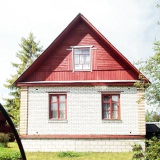 На фото: фасад индивидуального одноэтажного жилого дома, два окна в первом этаже и одно - в мансардном, фасад дома облицован кирпичом, кровля двускатная, стена фронтона мансарды - дощатая, перед домом - газон и садовые посадки