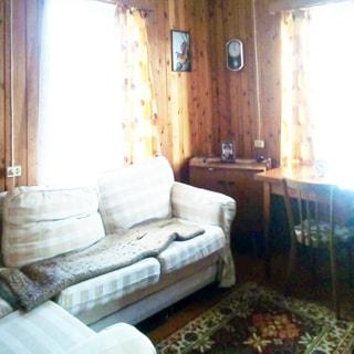 На фото: часть помещения жилой комнаты, два окна, между окон в углу - небольшой комод, справа от комода - письменный стол со стулом, слева от комода у окна - мягкий диван, стены отделаны вагонкой, на полу - ковер