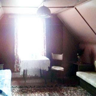 На фото: часть помещения жилой комнаты, одно окно, потолки мансардные разновысотные, у окна - стол со стулом, слева от окна у левой стены - диван, справа от окна у правой стены - второй диван, справа у окна в углу - журнальный столик, стены и потолок окрашены, на полу - ковер, на потолке - люстра