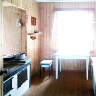 На фото: часть помещения столовой, одно окно, у окна обеденный стол с табуретом и стулом, слева от окна на стене небольшая кухонная полка, слева у стены в нише - дровяная печь с плитой, стены отделаны вагонкой, полы - дощатые