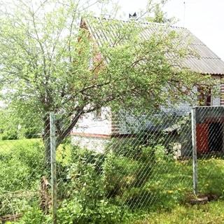 На фото: индивидуальный одноэтажный жилой дом на огороженном участке, ограждение - забор из сетки рабица, на участке перед домом - газон, садовые посадки и плодовые деревья, фасад дома облицован кирпичом, кровля - двускатная шиферная
