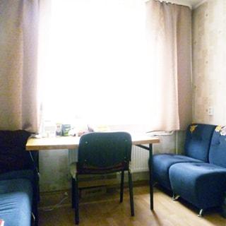 На фото: часть помещения кухни - столовая зона, одно окно, под окном радиатор батареи центрального отопления, у окна - обеденный стол, у стола - стул, справа и слева от стола у левой и правой стены - мягкие диваны, стены оклеены обоями, полы - линолеум
