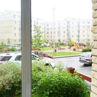 На фото: вид из окна во двор жилого микрорайона, перед домом высажены кустарники, придомовая территория асфальтирована, двор благоустроен, разбиты газоны, высажены деревья, обустроена детская площадка, пешеходные дорожки, уличное освещение, установлены садовые скамейки, у дома - припаркованные автомобили