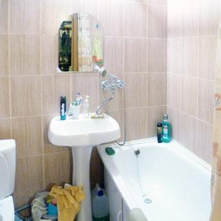 На фото: часть помещения совмещенного санузла, справа у стены - ванная, слева от нее керамическая раковина на керамической стойке, смеситель общий для раковины и ванны, над раковиной на стене - зеркало, слева от раковины - унитаз-компакт, стены облицованы керамической плиткой