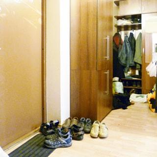 На фото: часть помещения прихожей, слева входная металлическая дверь, справа от входной двери - одежный шкаф, за ним еще один шкаф с открытой секцией для верхней одежды, полы - линолеум