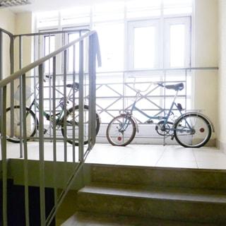 На фото: часть лестничной клетки, сплошное остекление, очень светло, ступени и площадка облицованы керамической плиткой, перила лестницы - металлические, у наружного окна - металлическое защитное ограждение, у окна - два велосипеда