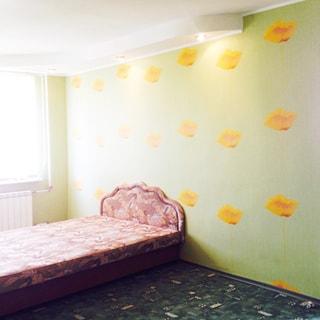 На фото: часть помещения жилой комнаты - спальни, одно окно, под окном радиатор батареи центрального отопления, у окна - двуспальная кровать с изголовьем, стены оклеены обоями, полы - ковролин, на потолке - точечные светильники