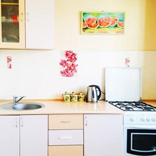 На фото: часть рабочей зоны кухонного пространства, кухонные столы-тумбы под общей столешницей, металлическая мойка со смесителем, четырехкомфорочная газовая плита с духовым шкафом, навесной кухонный шкафчик, фартук облицован плиткой