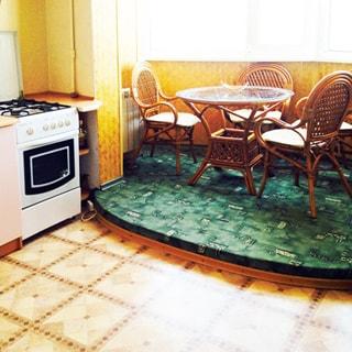 На фото: часть помещения кухни и эркера, большое окно на весь эркер, слева под окном - батарея центрального отопления, перед окном на небольшом подиуме стол из ротанга со стеклянной столешницей, вокруг стола - четыре стула из ротанга, пол в кухне - линолеум, пол на подиуме - ковролин, слева в углу - кухонная плита