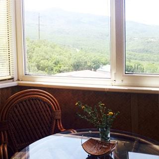 На фото: часть пространства эркера, на переднем плане журнальный столик с круглой стеклянной столешницей и стулом у стола, на столе - стеклянная ваза с полевыми цветами и плетеная фруктовница, большое окно, установлен стеклопакет, за окном виден лесной массив и горы, утопающие в зелени
