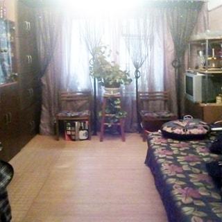 На фото: часть помещения жилой комнаты, одно окно, у окна - два стула и подставка с цветами, слева у стены - шкаф, справа у стены ближе к окну - стеллаж, на нижней полке стеллажа - телевизор, дальше от окна - диван, полы - линолеум
