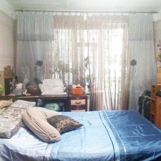 На фото: часть помещения жилой комнаты - спальни, большое окно, балконная дверь открыта, слева у окна - письменный стол, посреди комнаты двуспальная кровать с изголовьем к левой стене, справа от окна у стены - комод