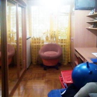 На фото: часть помещения жилой комнаты, одно окно, у окна - мягкое кресло, слева у окна в углу - холодильник, левее вдоль левой стены - шкаф-купе с зеркальными дверцами, справа от окна у правой стены - шкаф, письменный стол, навесные полки, на шкафу - телевизор, полы - паркет