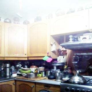 На фото: часть помещения кухни, кухонные столы-тумбы и навесные кухонные шкафы над ними, справа - четырехкомфорочная газовая плита, над ней - вытяжка, на столах - кухонная посуда, сверху на навесных полках - изделия из керамики