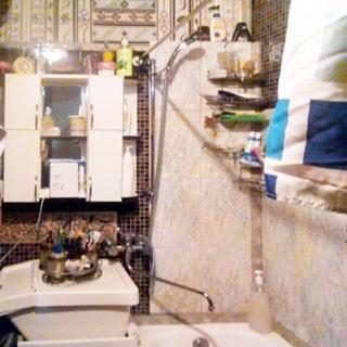 На фото: часть помещения ванной комнаты, справа у стены - ванная, слева от нее - керамическая раковина с общим смесителем для раковины и ванны, над раковиной на стене - навесной туалетный шкафчик с полочками и зеркалом, стены облицованы керамической плиткой