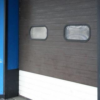 На фото: часть фасада здания с въездными воротами, ворота - секционные подъемные с двумя окошками, габарит для механизированной и ручной погрузочно-разгрузочной техники и механизмов