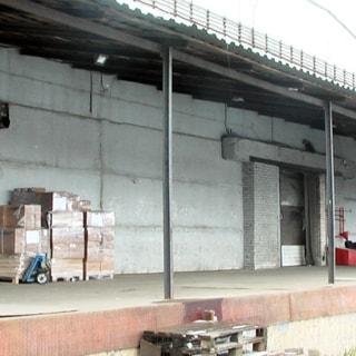 На фото: часть фасада складского здания с пандусом для загрузки-выгрузки грузовых автомобилей, стены фасада - панели, полы пандуса - бетонная стяжка, пандус закрыт стационарным односкатным навесом, кровля навеса - металлопрофиль, на пандусе обрудовано уличное освещение