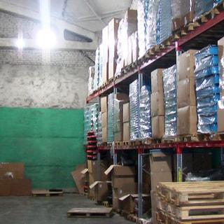 На фото: часть помещения склада, высокие сводчатые потолки, стены - панели и кирпичные, полы - бетонная стяжка, установлены многоярусные стеллажи для хранения пакетированных товаров и грузов с использованием грузовых паллет