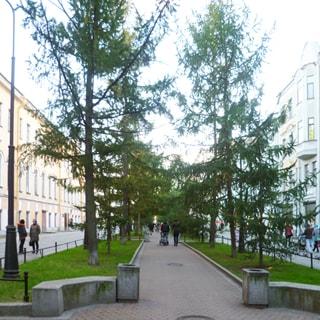 На фото: часть пешеходной зоны, мощеные дорожки, газоны, деревья, ограждения и урны, уличные фонари, справ и слева - жилые дома