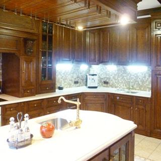 На фото: часть помещения кухни, встроенная кухонная мебель вдоль стены, остров с мойкой и столешницей, фасады - дерево, фартук - плитка, местное освещение, на столешнице в углу - кофеварка, полы - плитка