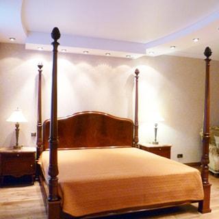 На фото: часть помещения жилой комнаты - спальни, прямо у стены - двуспальная кровать, слева и справа у изголовья - прикроватные тумбочки с настольными светильниками, правее у стены - кресло, на потолке - точечные светильники