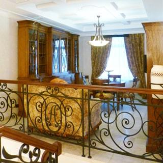 На фото: часть помещения комнаты под библиотеку, на переднем плане - решетчатое ограждение от лестничного пролета, на заднем плане - одно окно, слева у стены - книжный шкаф, у ограждения - мягкое кресло, посредине комнаты - круглый стол и четыре стула вокруг него, полы - плитка, на потолке - люстра