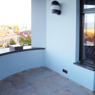 На фото: часть балкона, сплошное каменное ограждение с гранитным парапетом, полы - плитка, на стене - уличный светильник, вдали - улица, жилые дома и собор