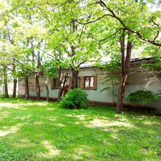 На летней фотографии: фасад одноэтажного нежилого кирпичного здания, с фасада - четыре окна, закрытых защитными решетками и дверь, перед зданием свободная дворовая территория - газон, кустарник, деревья