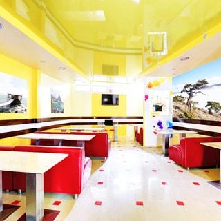 На фото: часть нежилого помещения для проведения конференций и презентаций, прямо у дальней стены - стол ведущего, за ним на стене - телевизионная панель, перед ним справа и слева в два ряда столы и мягкие кресла для слушателей, полы - плитка, стены - окрашены, на стенах - цветные репродукции, на потолке - точечные светильники