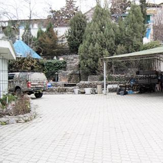 На фото: часть дворовой территории, сплошное мощение тротуарным камнем, клумбы и зеленые насаждения, уличное освещение, открытое место для парковки, справа - автомобильный навес, на дальнем плане соседние строения и дома