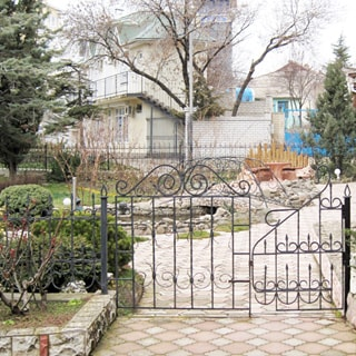На фото: входная калитка кованой ограды, за ней - небольшой благоустроенный двор, дорожки вымощены тротуарным камнем, высажены декоративные растения, кусты, деревья, устроены клумбы, небольшой пруд с мостком, установлены уличные скамейки для посетителей, за садом - соседние дом и строения