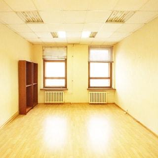 На фото: часть помещения офисного типа, два окна, под каждым окном - радиатор центрального отопления, слева от окна у стены - два книжных стеллажа, на окнах жалюзи, полы - линолеум, стены окрашены, потолки - подвесные, установлены потолочные люминесцентные офисные светильники