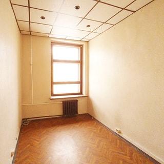 На фото: часть помещения комнаты без мебели, одно окно, под окном - радиатор центрального отопления, полы - линолеум, потолки - подвесные, установлены точечные светильники