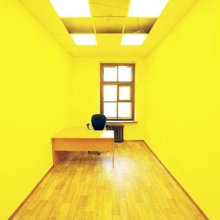 На фото: часть помещения комнаты офисного типа, одно окно, под окном - радиатор центрального отопления, слева от кона у стены - офисный стол с офисным креслом, полы - линолеум, стены окрашены, потолки - подвесные, установлены потолочные люминесцентные офисные светильники