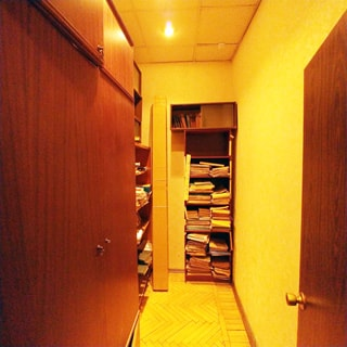 На фото: часть помещения офисного типа, прямо и слева у стен - стеллажи и шкафы для документов, полы - паркет, потолки - подвесные, установлены точечные светильники