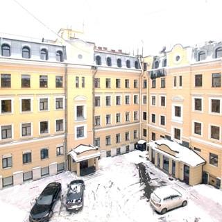 На зимнем фото: вид во двор из окна, небольшой асфальтированный двор, напротив - четырехэтажное здание с мансардой, парадная с козырьком, во дворе припаркованы легковые автомобили