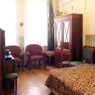 На фото: часть помещения жилой комнаты, два окна, у окна - два кресла, справа от окна у стены - книжный шкаф с дверцами, за шкафом - закрытая неиспользуемая дверь в соседнюю комнату, справа от шкафа - табурет и стул, правее - диван-кровать, напротив шкафа у противоположной стены - секретер, слева от секретера - табурет, полы - паркет, стены оклеены обоями