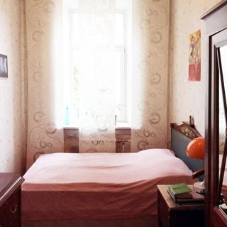 На фото: часть помещения жилой комнаты, одно окно, под окном - радиатор батареи центрального отопления, перед окном подголовником к правой стене - кровать, справа от кровати у стены - прикроватная тумбочка с ночником, правее - шкаф, напротив шкафа у противоположной стены - комод, на стене - эстампы, стены оклеены обоями