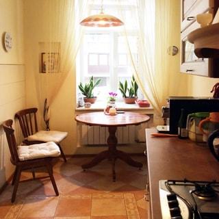 На фото: часть помещения кухни-столовой, одно окно, под окном - радиатор батареи центрального отопления, на подоконнике - декоративные растения, перед окном - круглый обеденный стол, слева у стола - два стула, справа у стены - встроенный кухонный гарнитур из тумб с общей столешницей и навесные шкафы, на столешнице - кофеварка, встроенная варочная газовая панель на четыре конфорки, пол - плитка, на потолке - кухонная люстра