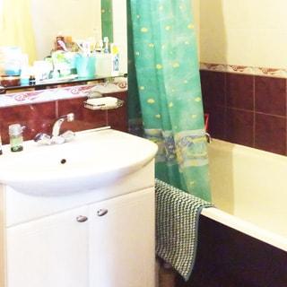 На фото: часть помещения санузла, прямо у стены - керамическая раковина на тумбе со своим смесителем, над раковиной - зеркало с полкой, на полке - туалетные принадлежности, справа у стены - ванная со своим смесителем и занавеской, стены - облицованы керамической плиткой