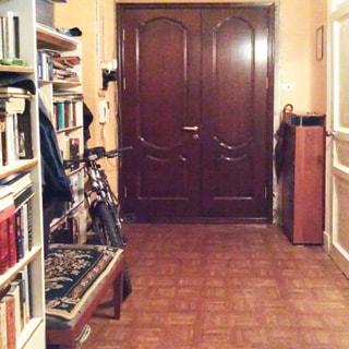 На фото: часть помещения прихожей, прямо - входная металлическая двустворчатая дверь, справа от двери у стены - шкафчик для обуви, правее - дверь в соседнее помещение, слева от двери на стене - электрический счетчик и домофон, левее - стеллажи с книгами, тумба и велосипед, полы - линолеум, стены оклеены обоями
