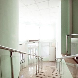 На фото: часть нежилого помещения - холла, лестница вниз с ограждением и перилами из металла и стекла, внизу помещение холла со вторым светом на цокольный и первый этаж, входная группа из металла и стекла, над входом блок кондиционера, выше окна второго света, внизу справа - открытая дверь в соседние помещения цокольного этажа, стены окрашены, потолки - подвесные, полы и ступени лестницы облицованы керамической плиткой