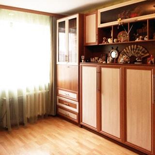 На фото: часть помещения жилой комнаты, одно большое окно, под окном - радиатор батареи центрального отопления, справа от окна вдоль стены - мебельный гарнитур со стеклянными и сплошными фасадами, открытыми и закрытыми полками, полы - ламинат