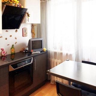 На фото: часть помещения кухни, одно окно и балконная дверь, под окном - радиатор батареи центрального отопления, слева от окна вдоль стены - кухонный гарнитур из тумб-столов с общей столешницей, встроенной варочной поверхностью и духовым шкафом, над столешницей на стене - навесные кухонные шкафы и вытяжка, на столешнице у окна небольшой телевизор, справа от окна - обеденный стол и два стула у него, полы - ламинат, фартук - плитка