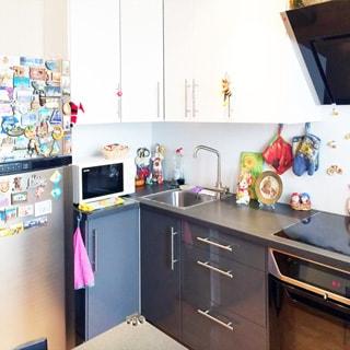 На фото: часть помещения кухни, вдоль стены кухонный гарнитур из тумб-столов с общей столешницей и встроенной варочной поверхностью и духовым шкафом, над столешницей на стене - навесные кухонные шкафы и вытяжка, в угловой секции - металлическая мойка со смесителем, слева от нее на столешнице - микроволновая печь, левее - двухкамерный холодильник, фартук - плитка