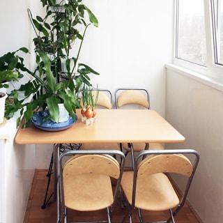 На фото: часть пространства застекленного балкона, на балконе - складной столик на четверых и четыре стула, на столе комнатные растения, окна - стеклопакеты
